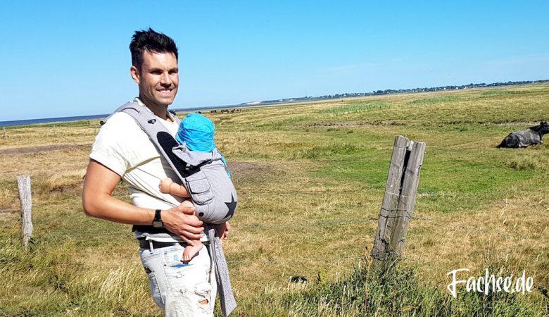 Mann trägt Baby in Babytrage