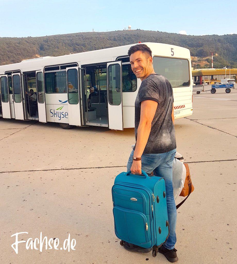 Mann mit Koffer vor Bus
