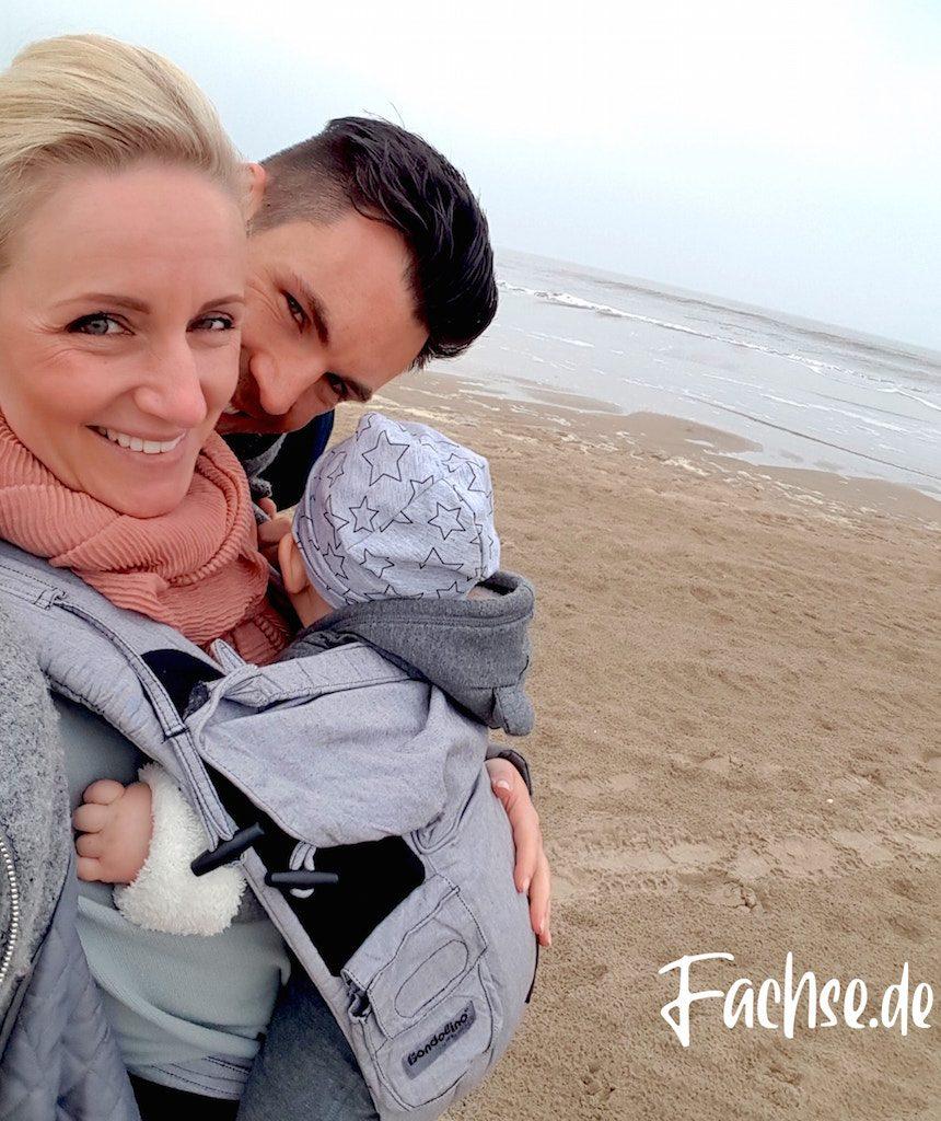 Mann und Frau mit Baby in Trage an Strand