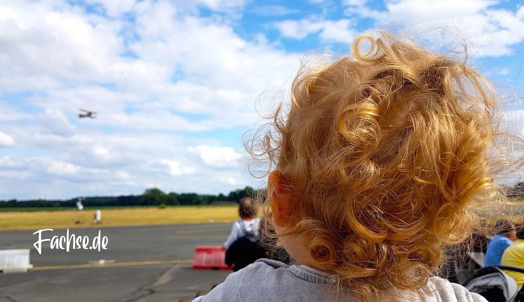 Kleiner Junge von hinten, Flugzeug im Himmel über Flugplatz