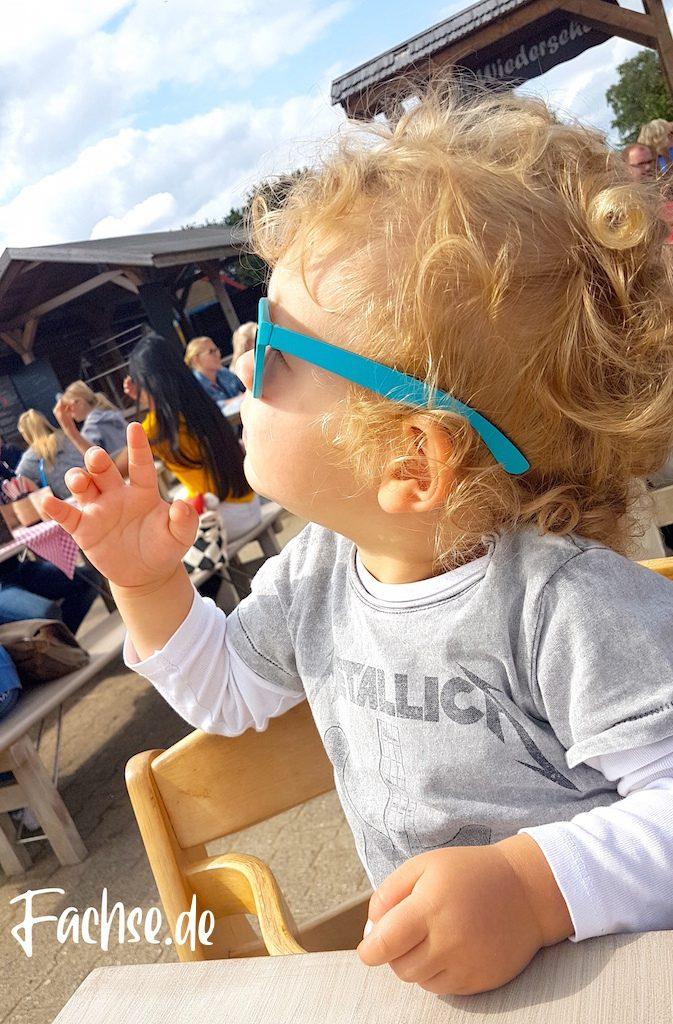 Kleiner Junge mit blauer Sonnenbrille und Metallica T-Shirt, sitzt im Biergarten