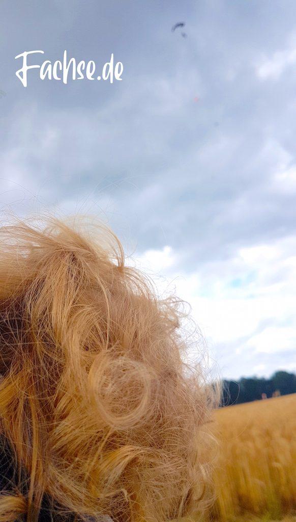 Blonde Locken im Vordergrund. Fallschrimspringer unscharf im Himmel
