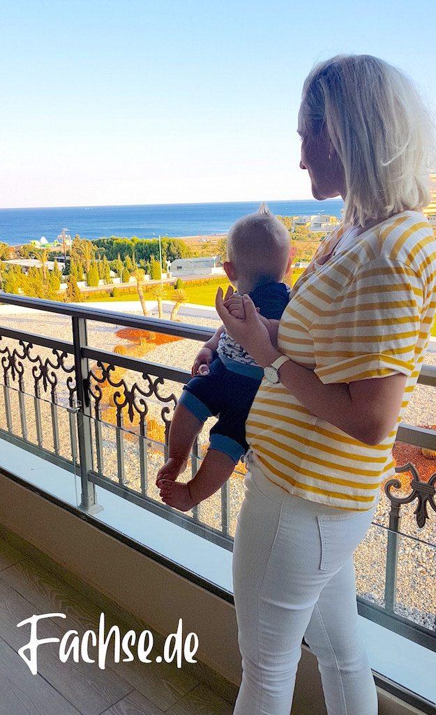Frau mit Kind auf einer Hotel-Terrasse, Meerblick Rhodos