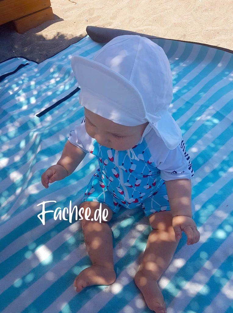 Baby mit Schwimmanzug und Sonnenhut am Strand