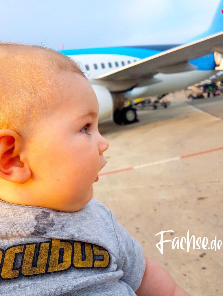 Baby vor Flugzeug