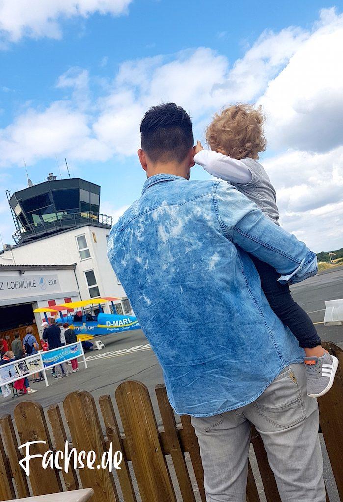 Vater hat Sohn auf dem Arm, zu sehen von hinten