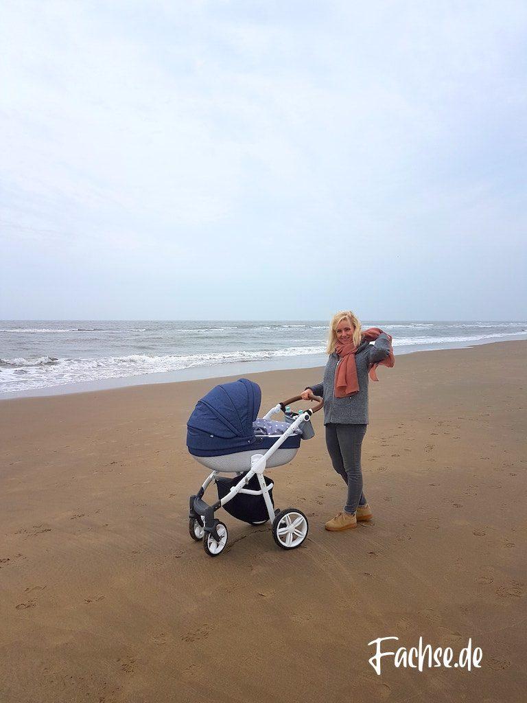 Frau mit Kinderwagen am Meer