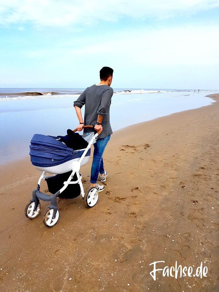 Mann mit Kinderwagen am Strand