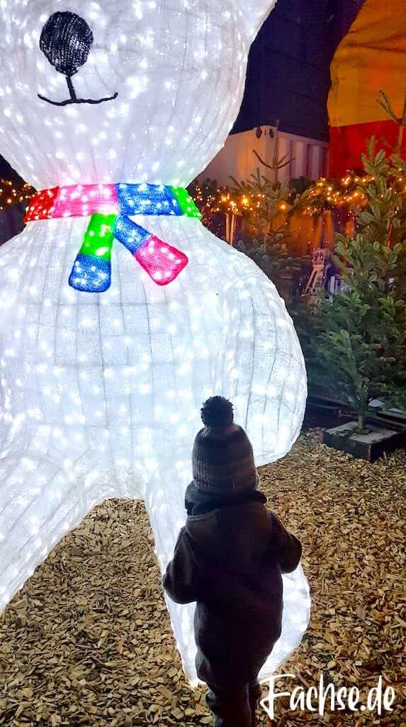 Leuchtender Bär auf dem Weihnachtsmarkt und Kleinkind