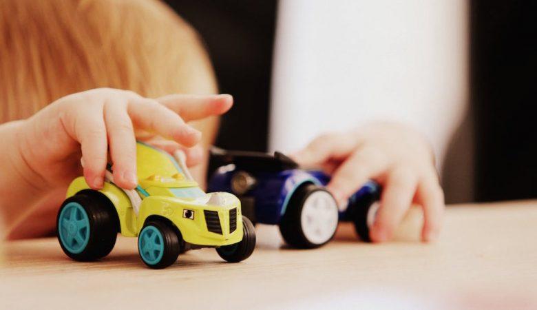 Kind spielt mit zwei Spielzeugautos