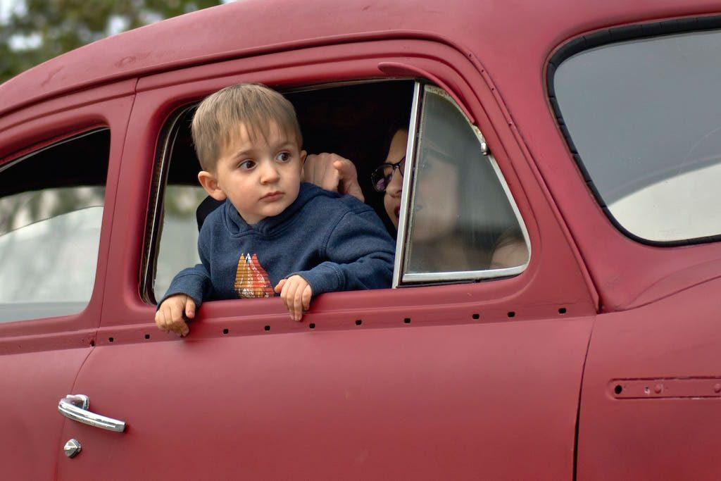 Kind sitz auf Beifahrersitz und guckt aus rotem Auto