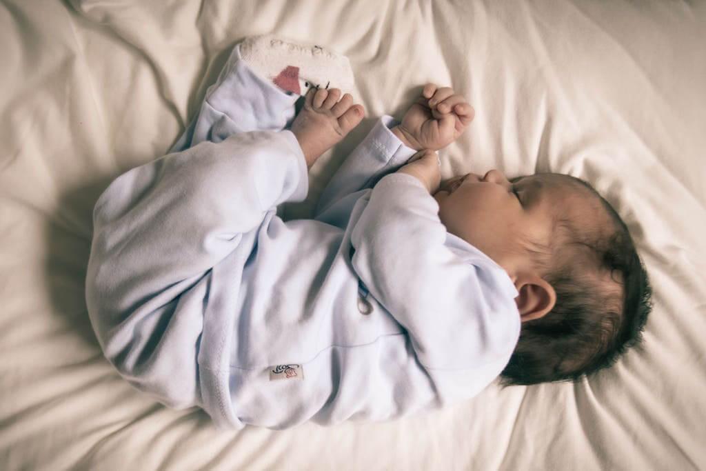 Baby schläft im Bett Strampler