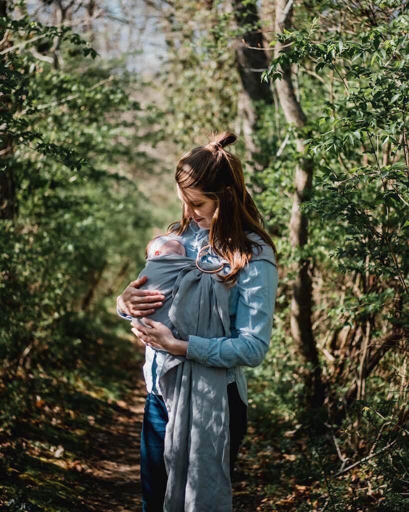Mutter trägt Baby in Tragetuch im Wald Bäume Babytrage