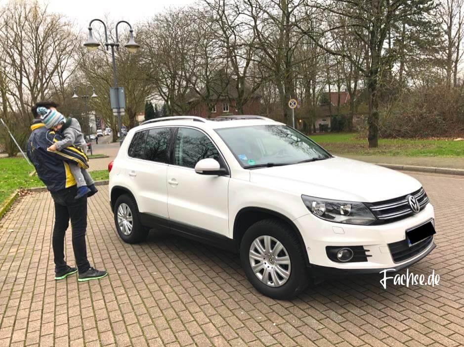 Mann mit Kind vor VW Tiguan weiß