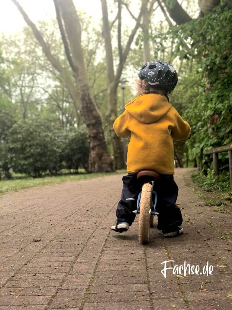 Kind mit Helm auf Laufrad von hinten