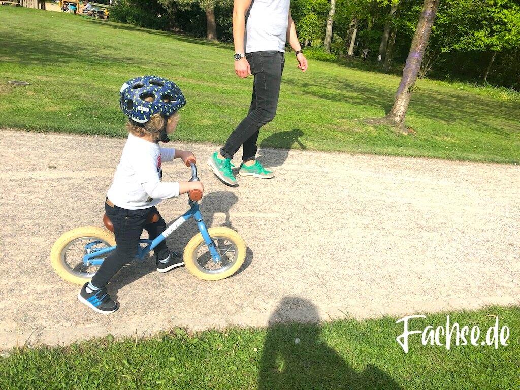 Vater und Sohn im Park Kinderhelm Laufrad Abus Veloretti