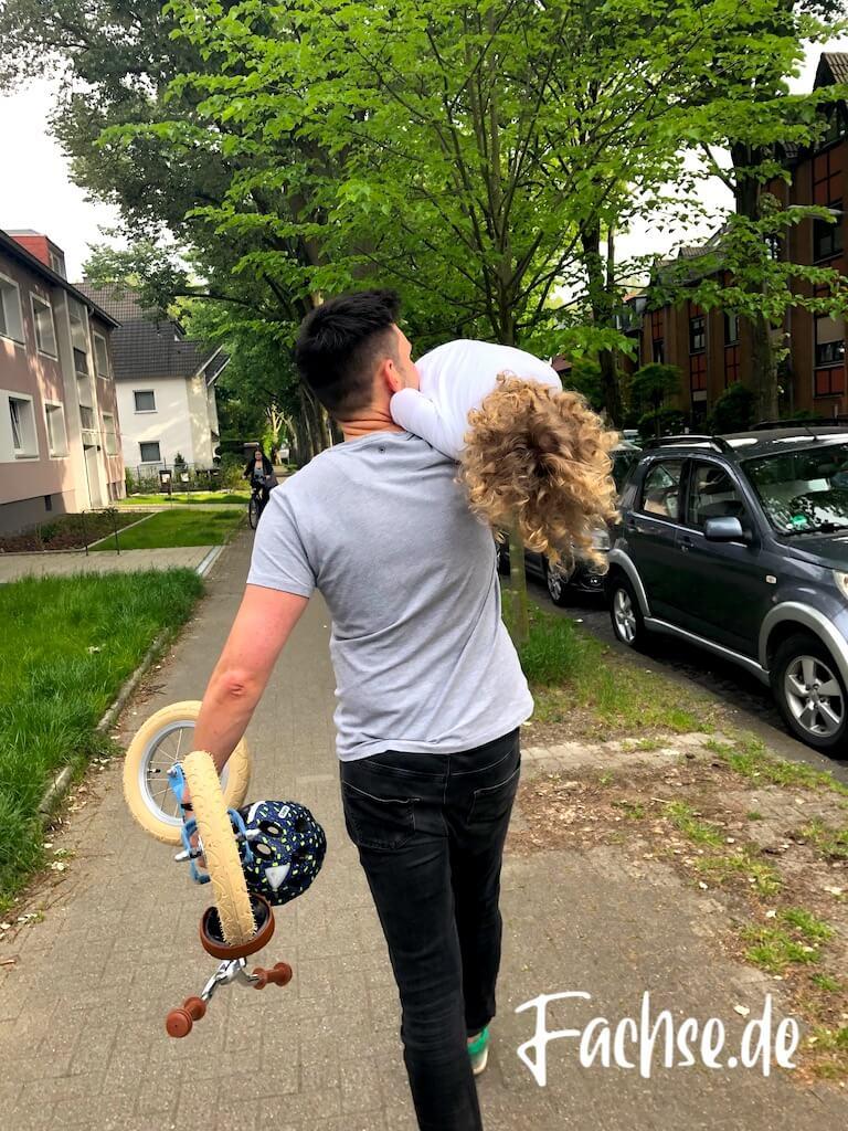 Mann Kind Vater und Sohn Laufrad Lockenkopf