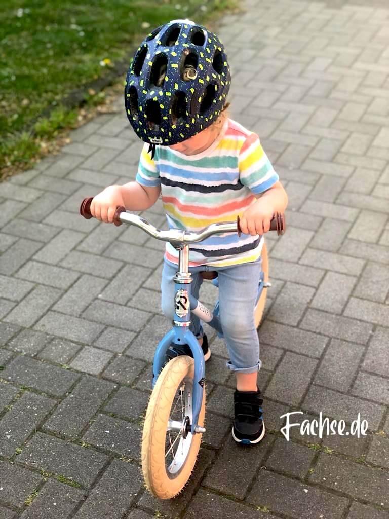Kind mit Helm auf Laufrad von vorne
