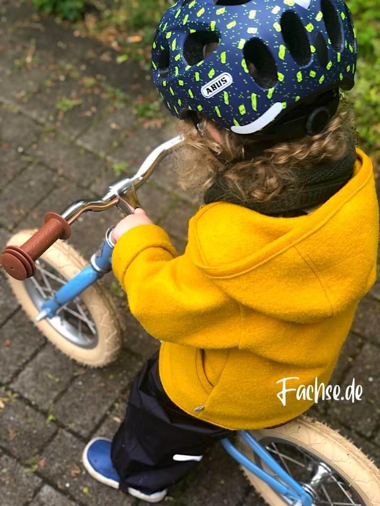 Kind mit Helm auf Laufrad